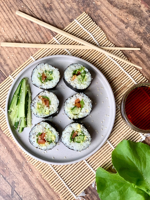 six vegan sushi rolls on a plate, on a bamboo mat with chopsticks next to it