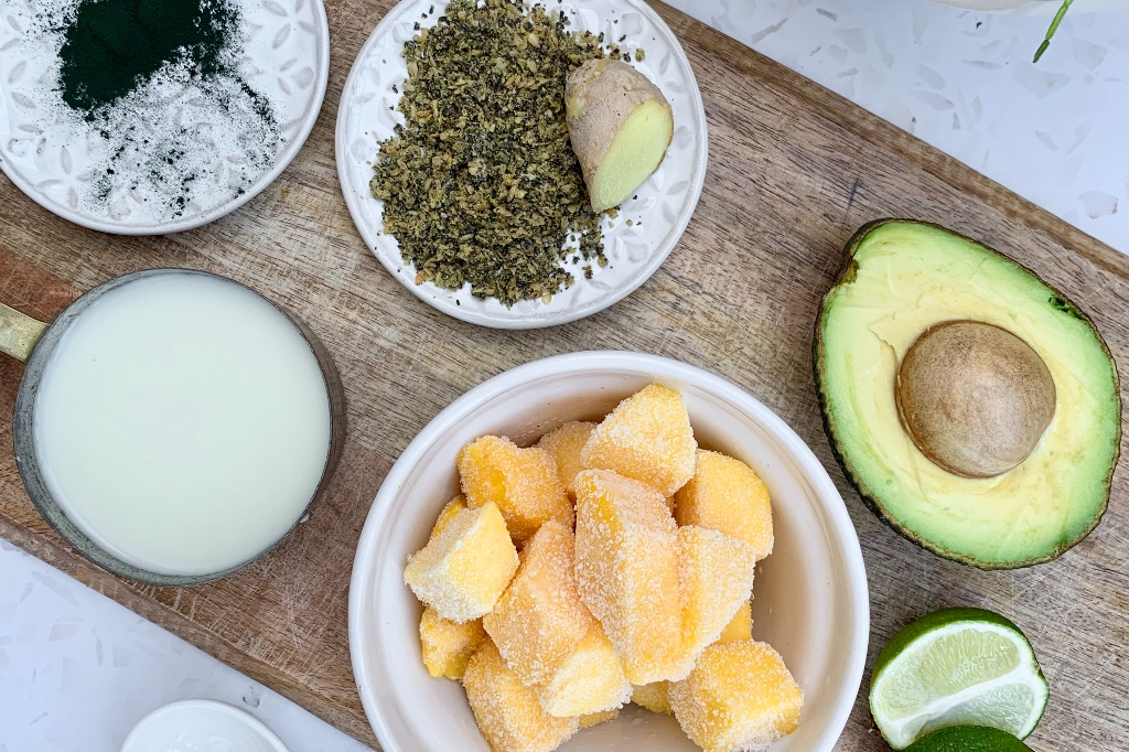 all of the ingredients for the green smoothie recipe presented on a wooden chopping board