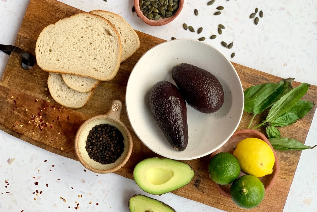 a variety of ingredients for the avocado toast recipe in a flatlay, including avocado, bread, black peppercorns and fresh basil