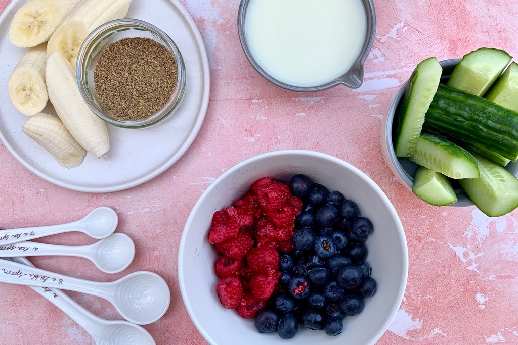 all of the ingredients for the berry smoothie recipe: blueberries, raspberries, cucumber, banana, oat milk and flaxseeds