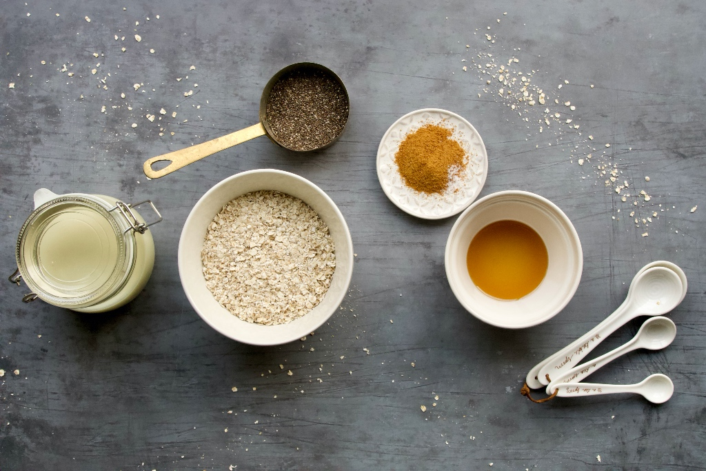 ingredients for the apple cinnamon overnight oats base recipe on a grey background. oats, oat milk, chia seeds, coconut sugar and maple syrup