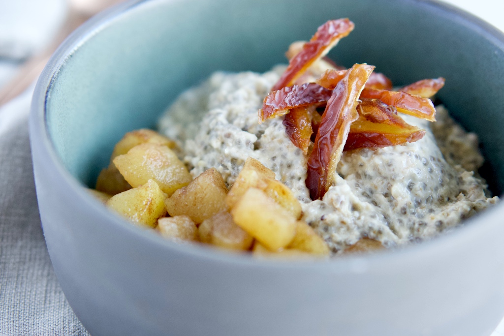 a close up of the apple cinnamon overnight oats in a grey bowl with chopped dates on top