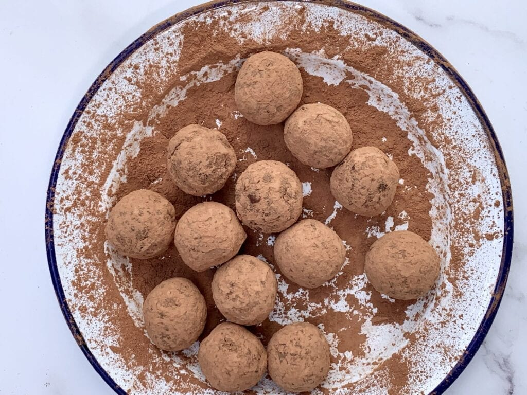 a plate of vegan salted caramel fudge energy balls coated in cacao powder