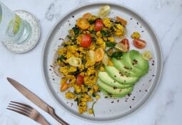 tofu scramble from above on a plate with spinach, toast, avocado and tomatoes