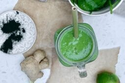 top down image of the final green smoothie recipe in a glass jar with a bamboo straw, with ingredients on the surface around it.