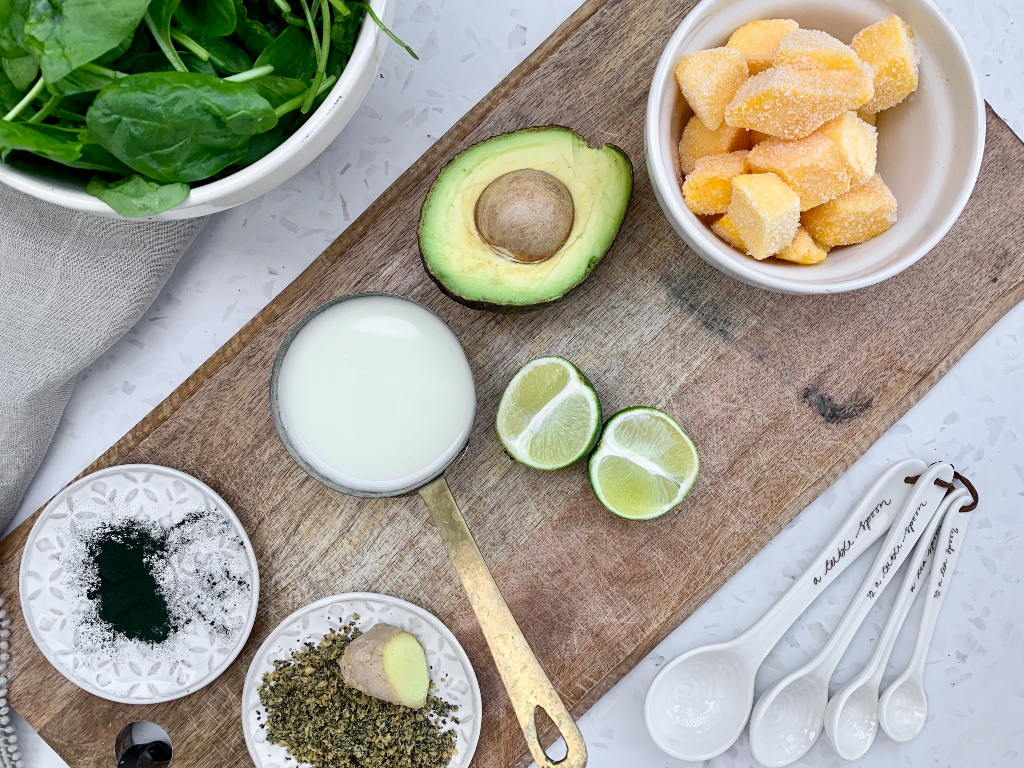 flat-lay of the ingredients for the green smoothie recipe on a wooden chopping board