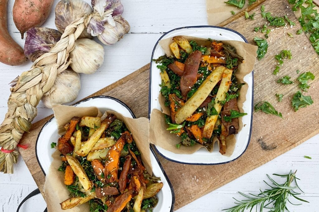 cooked healthy air fryer recipe fries with kale in white tin dishes on a wooden chopping board