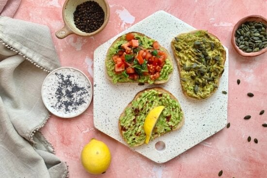 avocado toast recipe, all three finished, and presented on a hexagonal white stone platter with a few ingredients in dishes around the edge
