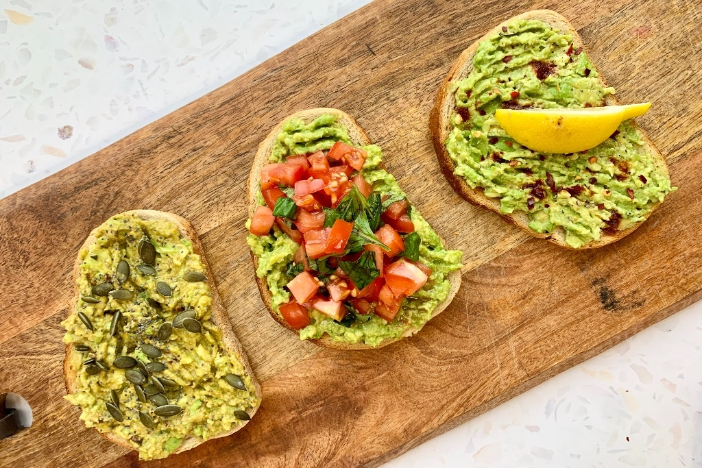 all three final recipes on toast presented top down on a wooden chopping board