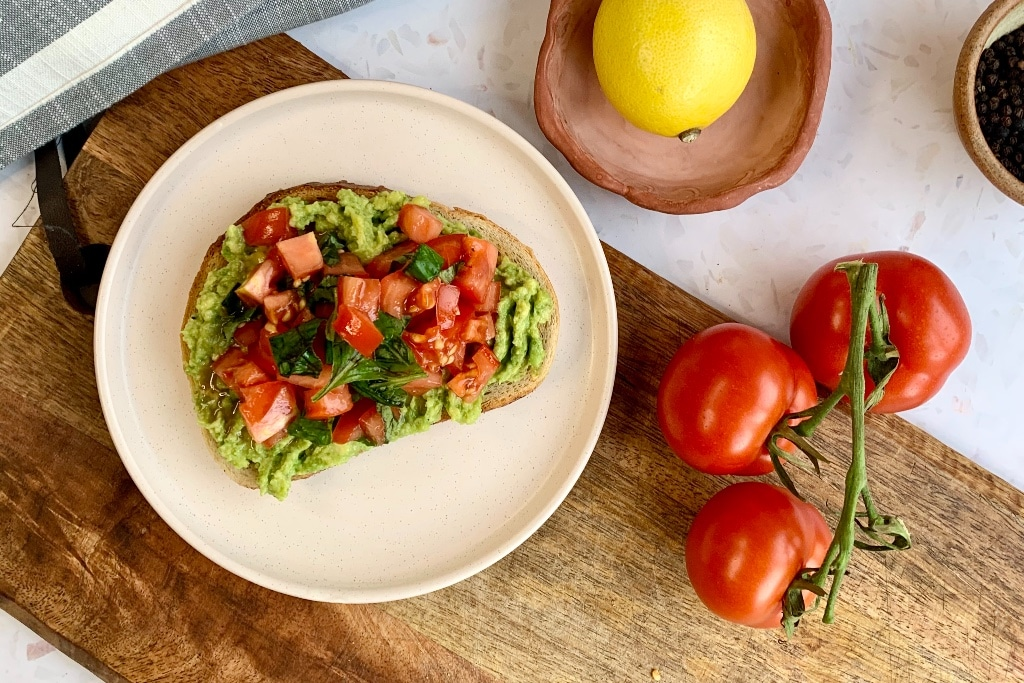 fresh tomato and basil on avocado toast, presented on a wooden chopping board with fresh tomatoes on the vine and a lemon next to it