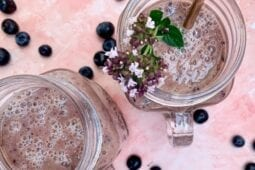 the berry smoothie recipe in glass jars with blueberries