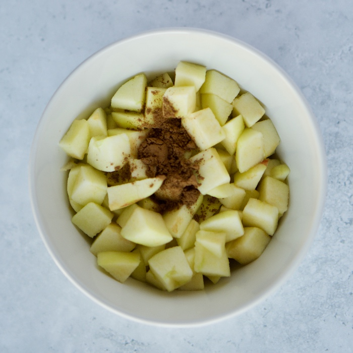 chopped raw apples in a bowl with cinnamon sprinkled over ready to be mixed