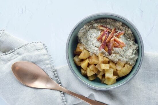 apple cinnamon overnight oats in a grey bowl next to a copper spoon, ready to be eaten