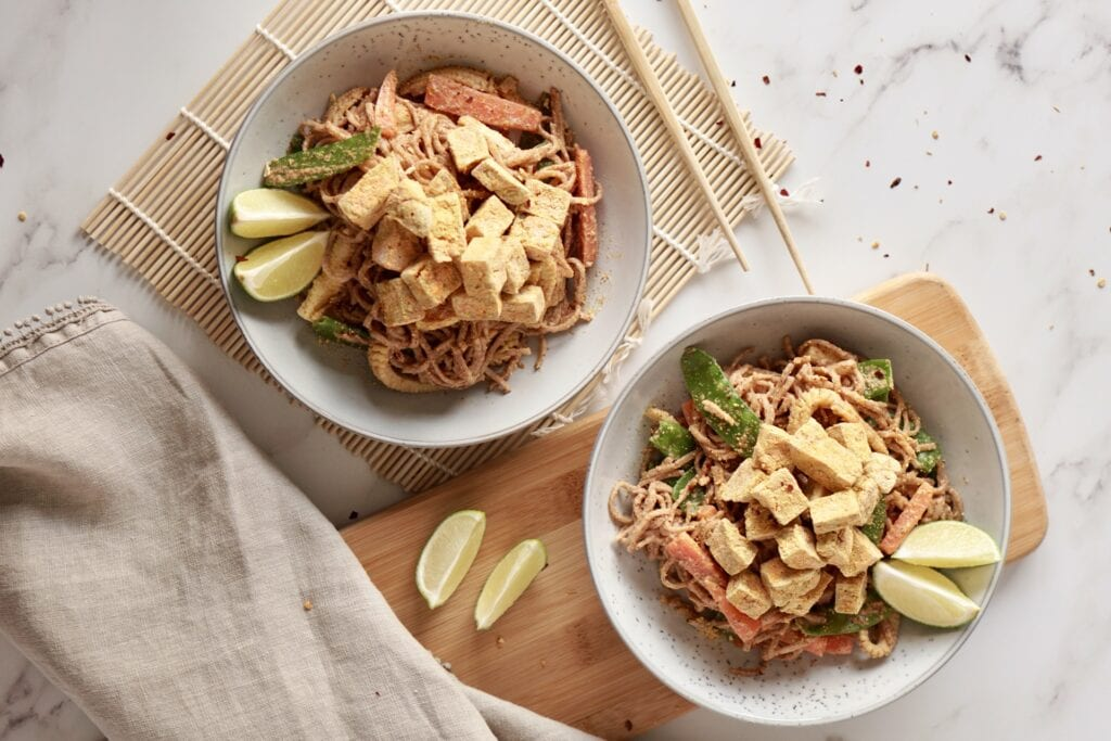 two bowls of tofu in peanut sauce on a marble background and bamboo chopping board next to chopsticks and wedges of lime