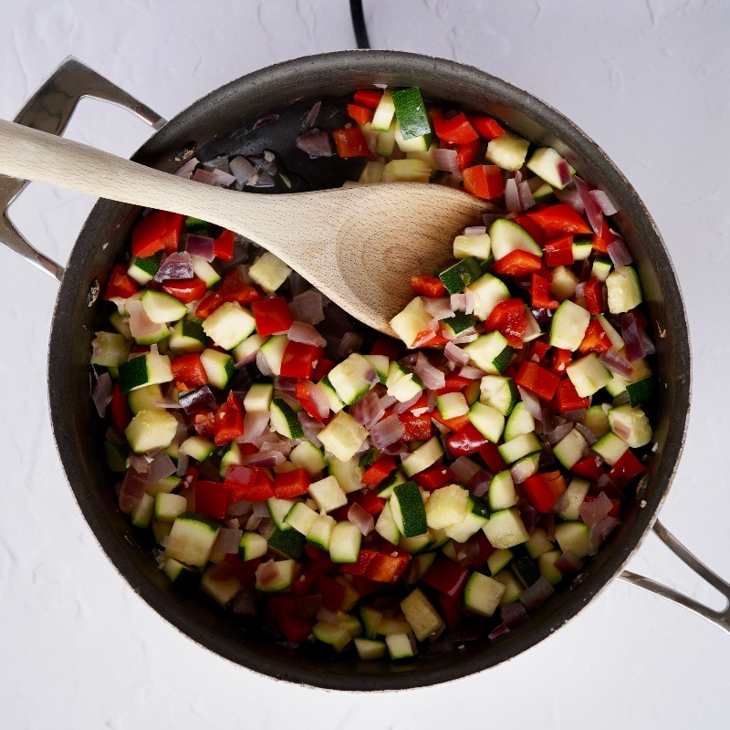 the vegetables; red bell pepper, courgette, onion and garlic in a large pan being stirred with a wooden spoon