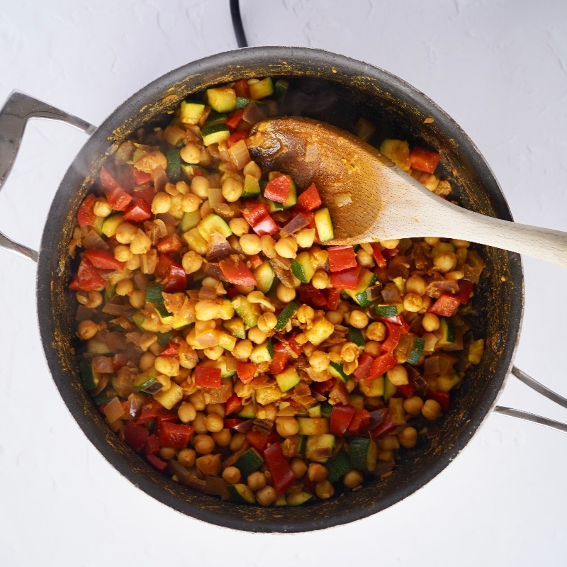the vegetable ingredients plus the chickpeas and spices in a large pan with a wooden spoon resting in it