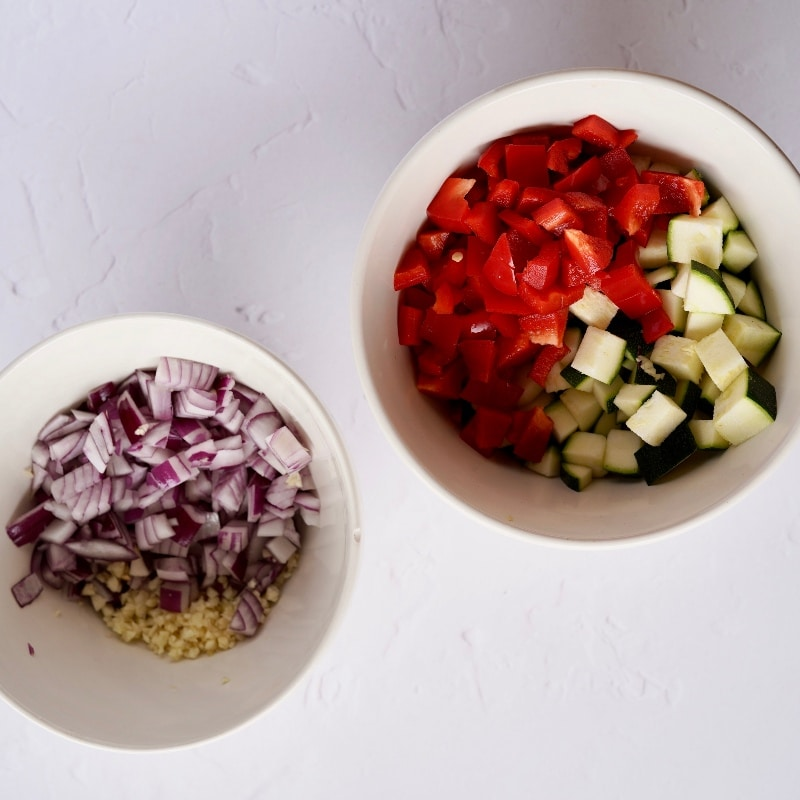 the chopped uncooked vegetable ingredients: red bell pepper, courgette, onion and crushed garlic