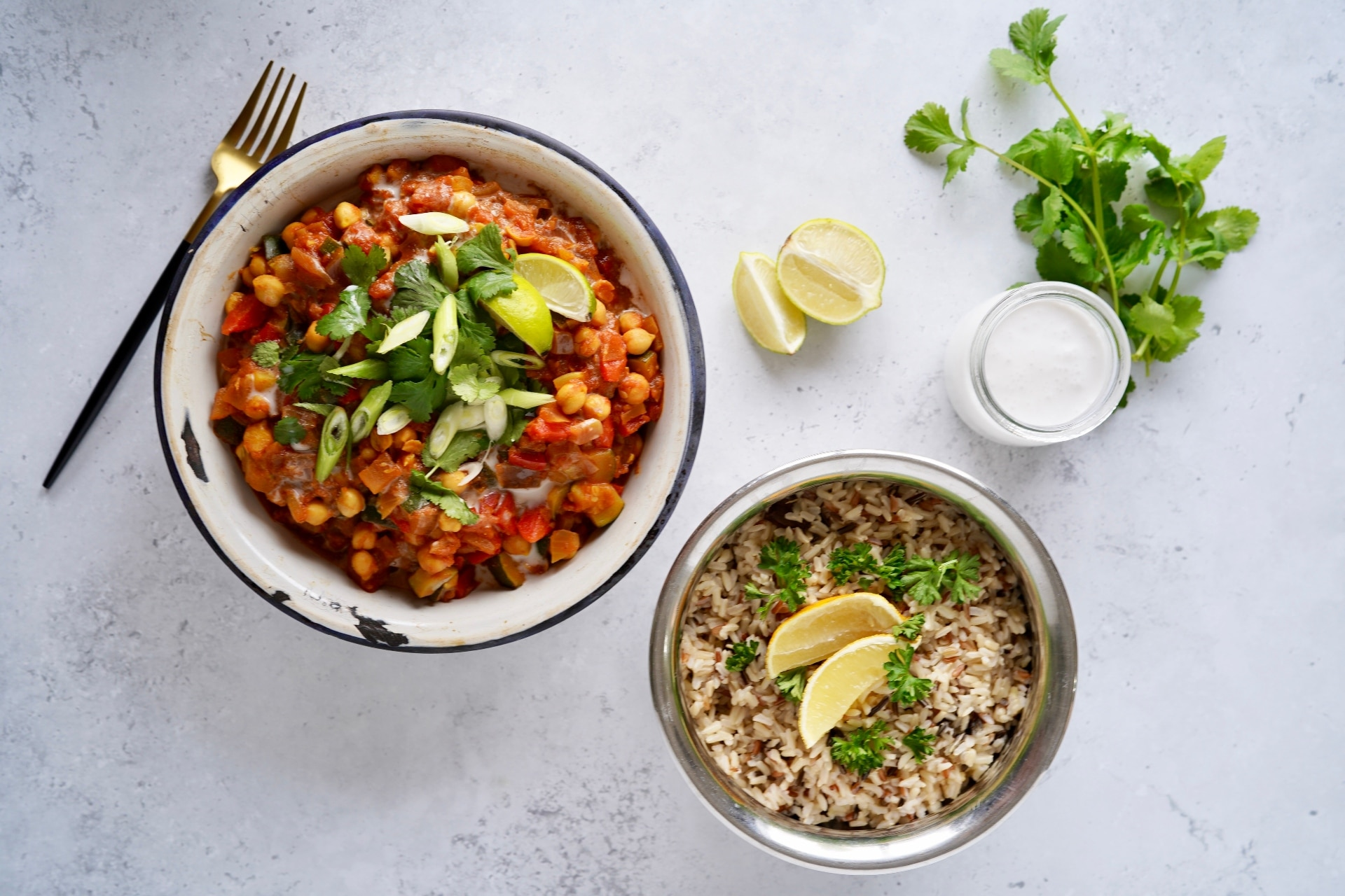 the final vegan Indian curry recipe topped with limes, coriander, and spring onion in a metal dish next to a bowl of wild rice topped with sprigs of fresh parsley and two lime wedges. A glass pot of coconut milk is next to the rice with some fresh sprigs of coriander alongside