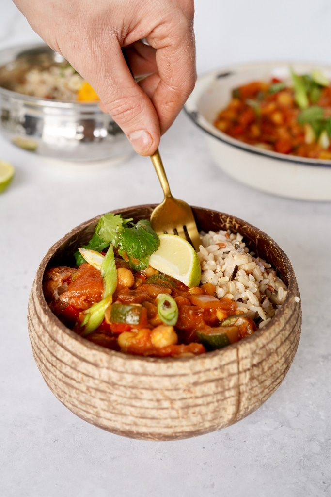 a hand is using a fork to dip into a bowl of vegan Indian curry recipe served with wild rice