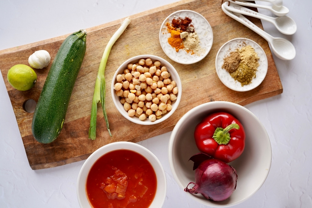 ingredients for the vegan Indian curry recipe laid out on a wooden chopping board