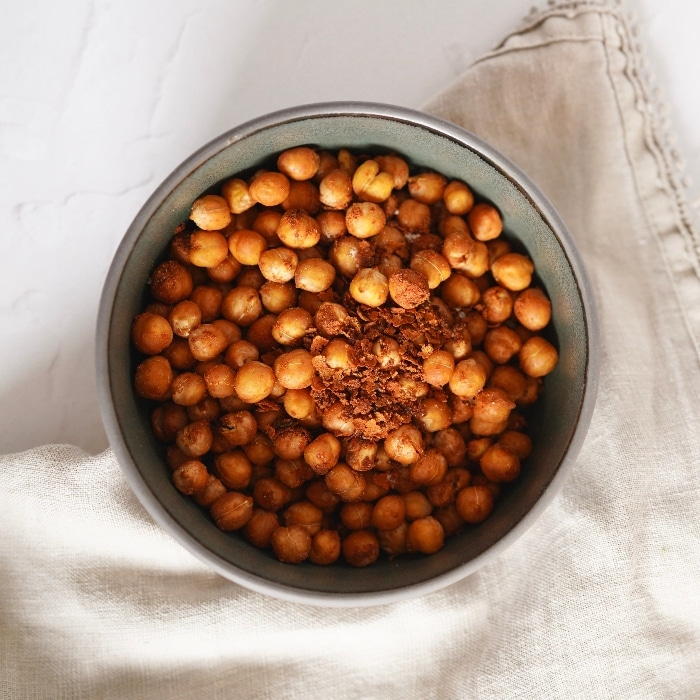 a bowl of cooked air fryer chickpeas on a cream cloth