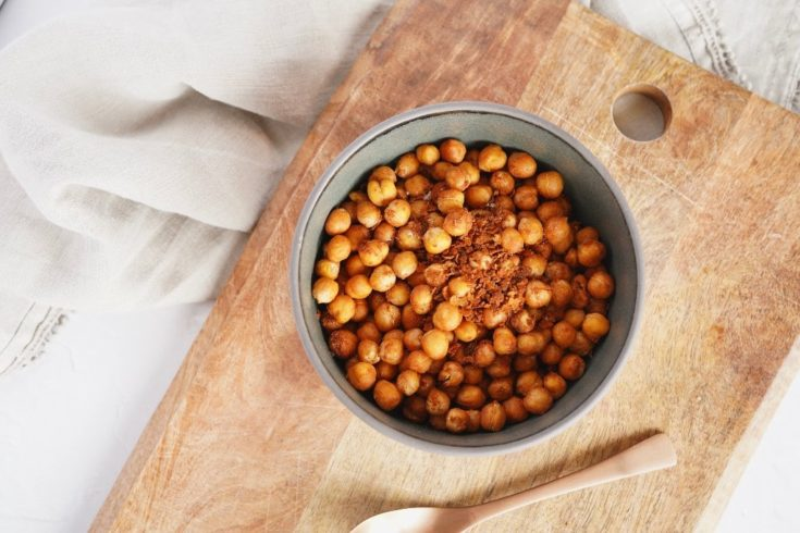 a bowl of the cooked air fryer chickpeas on a wooden chopping board with a copper spoon next to the bowl
