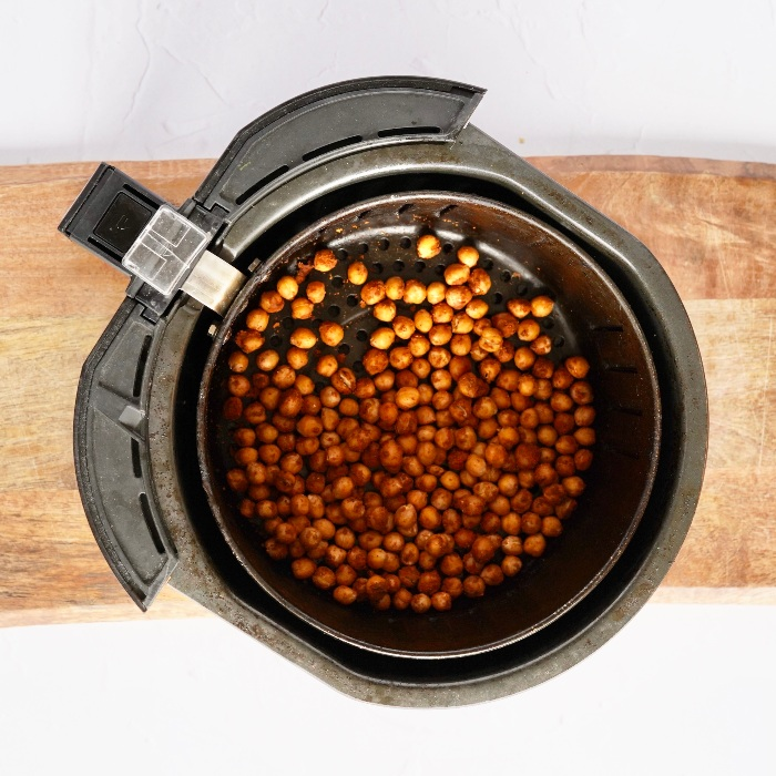 the air fryer chickpeas half way through cooking, in the air fryer tray.
