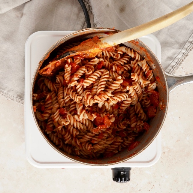 a pan of the pasta in a pan mixed with the chipotle pasta sauce, with a wooden spoon in the pan