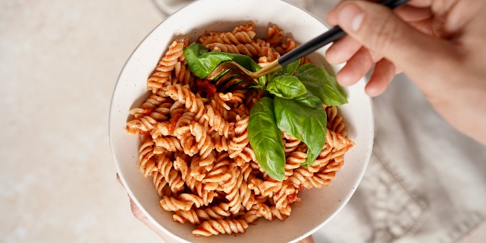 a bowl of the chipotle pasta sauce with some pasta spirals in a bowl with someone dipping a fork into it