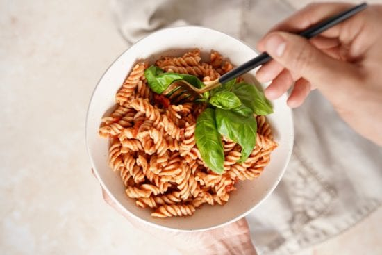 finished chipotle pasta sauce recipe in a bowl with someone dipping a fork into it. Some leaves of fresh basil garnish the top of the dish