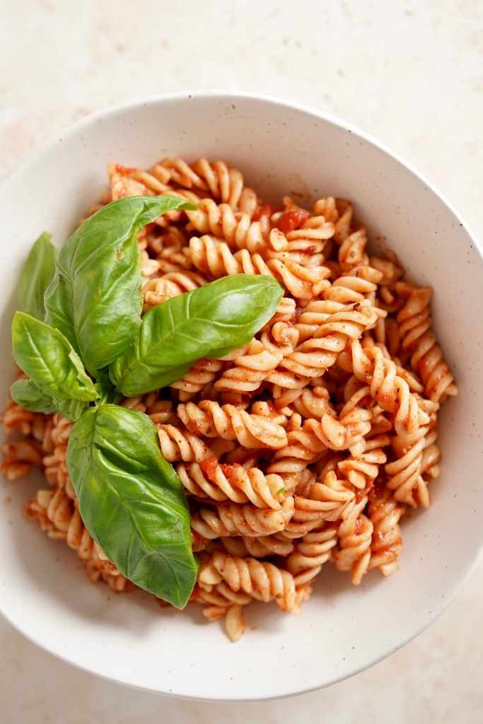 finished chipotle pasta sauce recipe in a bowl on a sandstone backdrop. Some leaves of fresh basil garnish the top of the dish