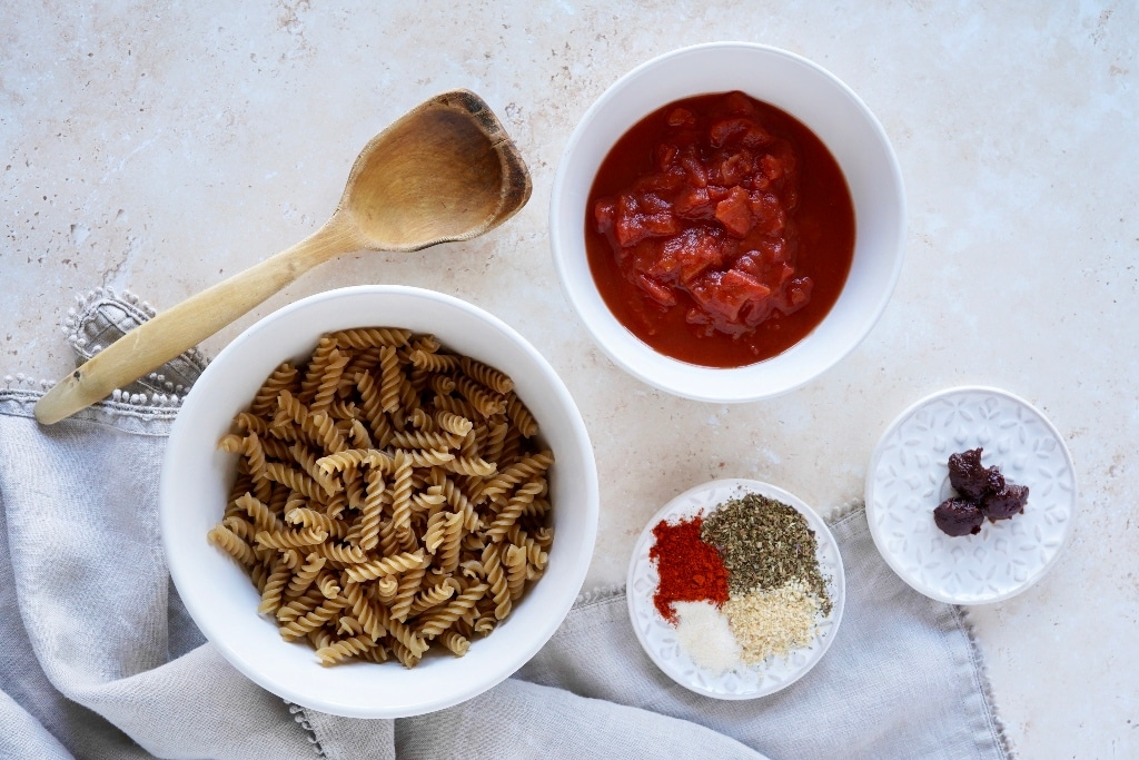 all of the ingredients for the spicy chipotle pasta sauce recipe on a sandstone background; brown rice pasta, tinned tomatoes, spices and chipotle paste