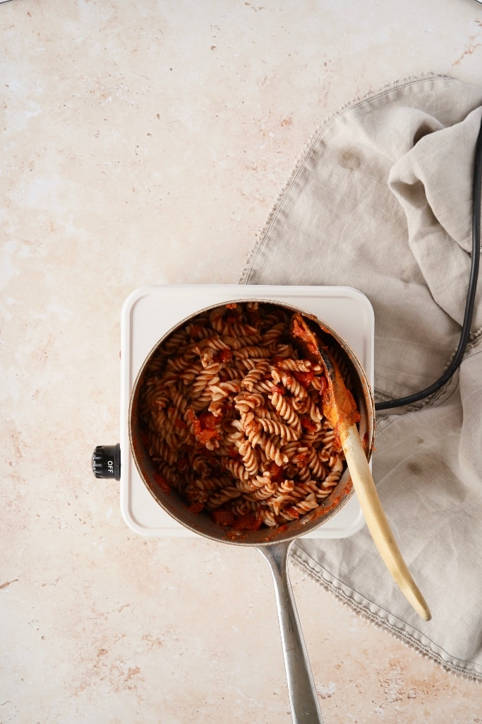 a pan of the spicy vegan chipotle pasta in a pan mixed with the chipotle pasta sauce, with a wooden spoon in the pan