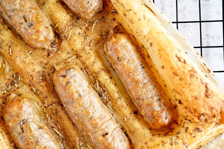 a close up of the cooked vegan toad in the hole showing golden brown puff pastry and cooked golden vegan sausages on a black wire cooling rack