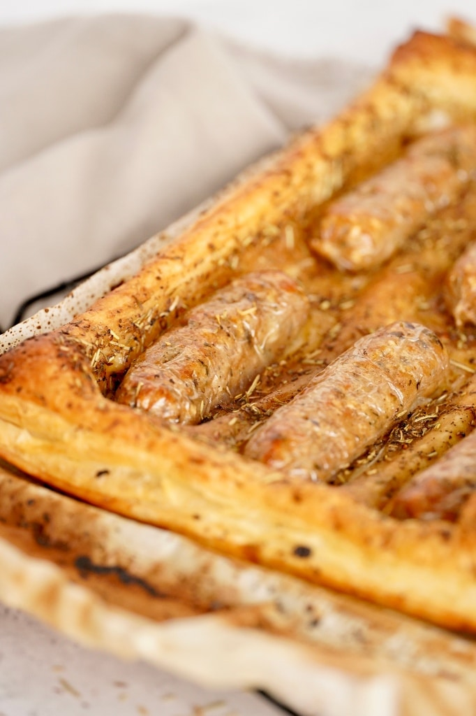 a close up of the cooked vegan toad in the hole showing golden brown puff pastry and cooked golden vegan sausages