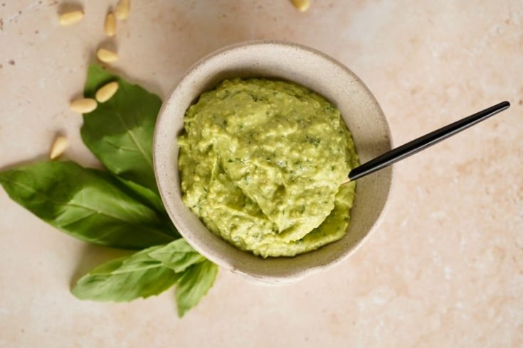 the oil-free pesto in a white ceramic dish with a small spoon in it. Basil leaves and pine nuts are on the surface around it.