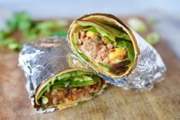 two halves of a vegan jackfruit pulled pork wrap, stuffed with jackfruit mix, lettuce and hummus, and wrapped in tin foil, laid out on a wooden chopping board
