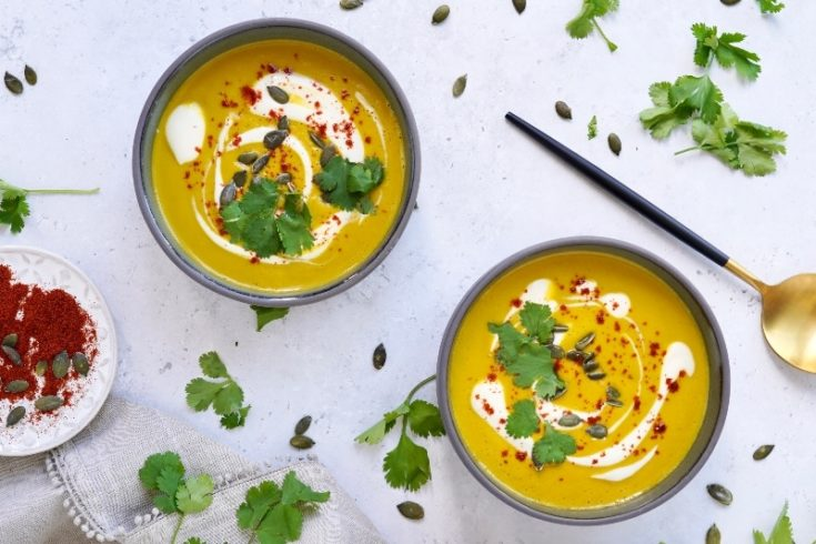 two bowls of the vegan carrot and coriander soup with garnish, on a surface with fresh coriander and pumpkin seeds around it.