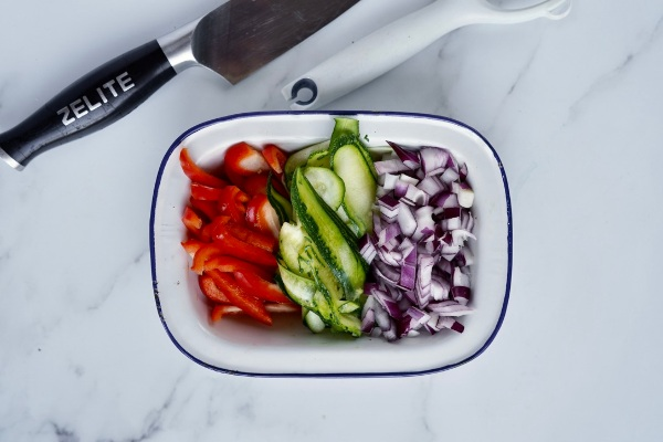 chopped red bell pepper, courgette and red onions in a rectangular tin dish with a knife next to the dish