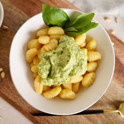 a large serving of the pesto on gnocchi in a white bowl, served with three fresh basil leaves as garnish.