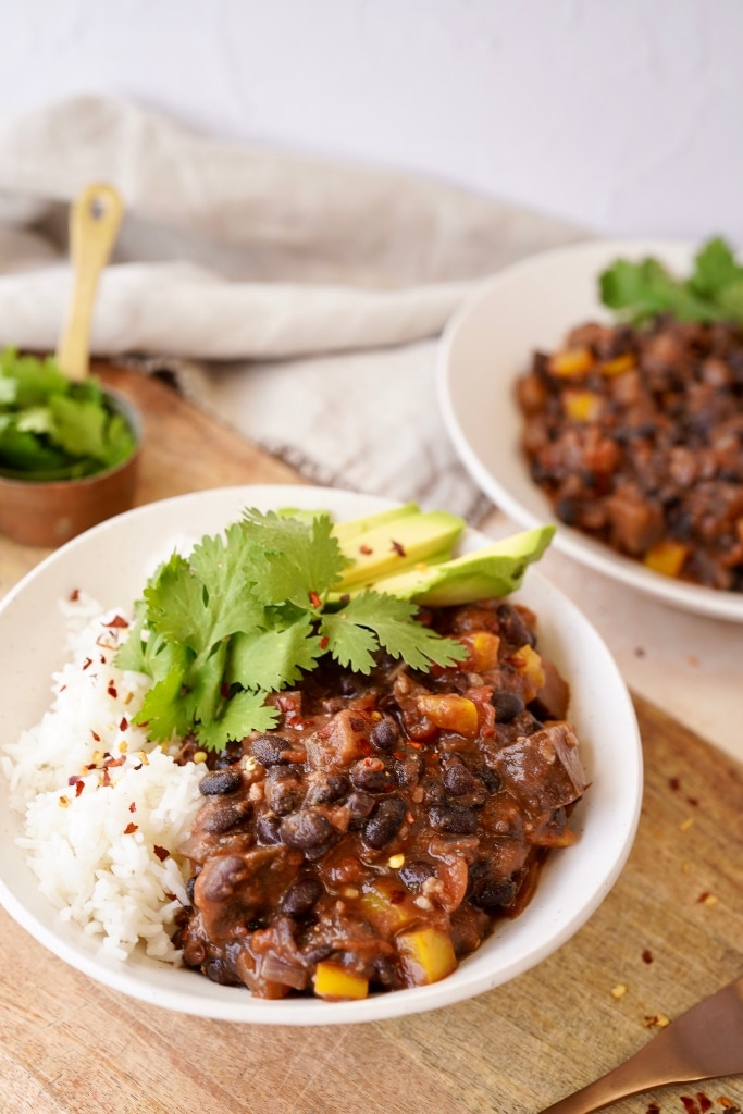 vegan black bean chili in a bowl served with rice, avocado and cilantro, with a bowl of extra chili behind it