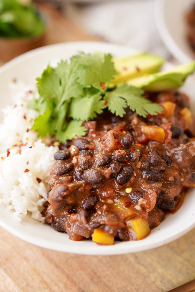 vegan black bean chili in a bowl served with rice, avocado and cilantro and chili flakes