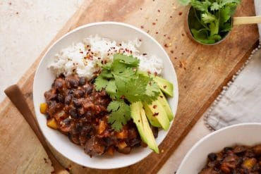 black bean chili in a bowl served with rice, avocado and cilantro, on a chopping board