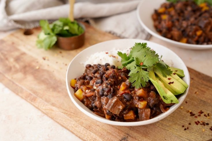 vegan black bean chili in a bowl served with rice, avocado and cilantro