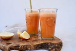 two glasses of carrot apple and ginger juice on a wooden board with chopped apple next to it