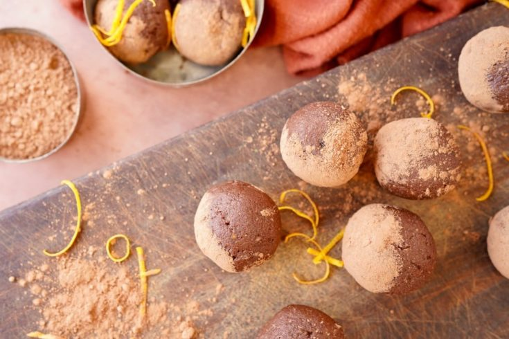 chocolate orange energy balls dusted with cacao on a chopping board with orange rind and cacao around them