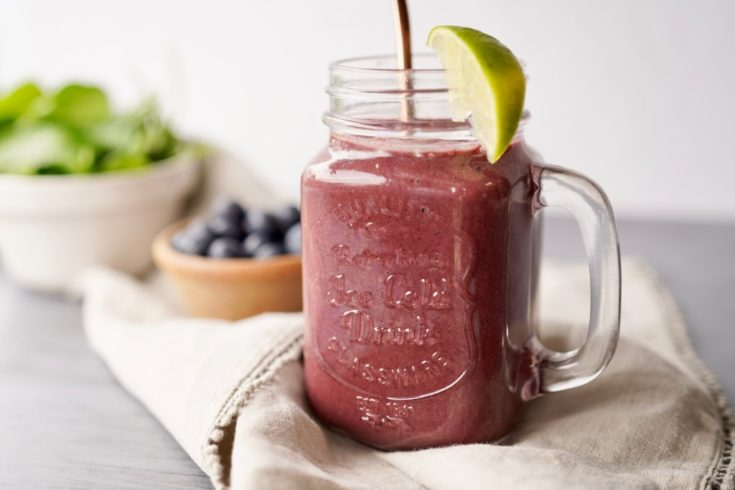 healthy blueberry smoothie in a glass with a wedge of lime to serve. blueberries and spinach leaves are next to the glass, which is on a natural piece of cloth