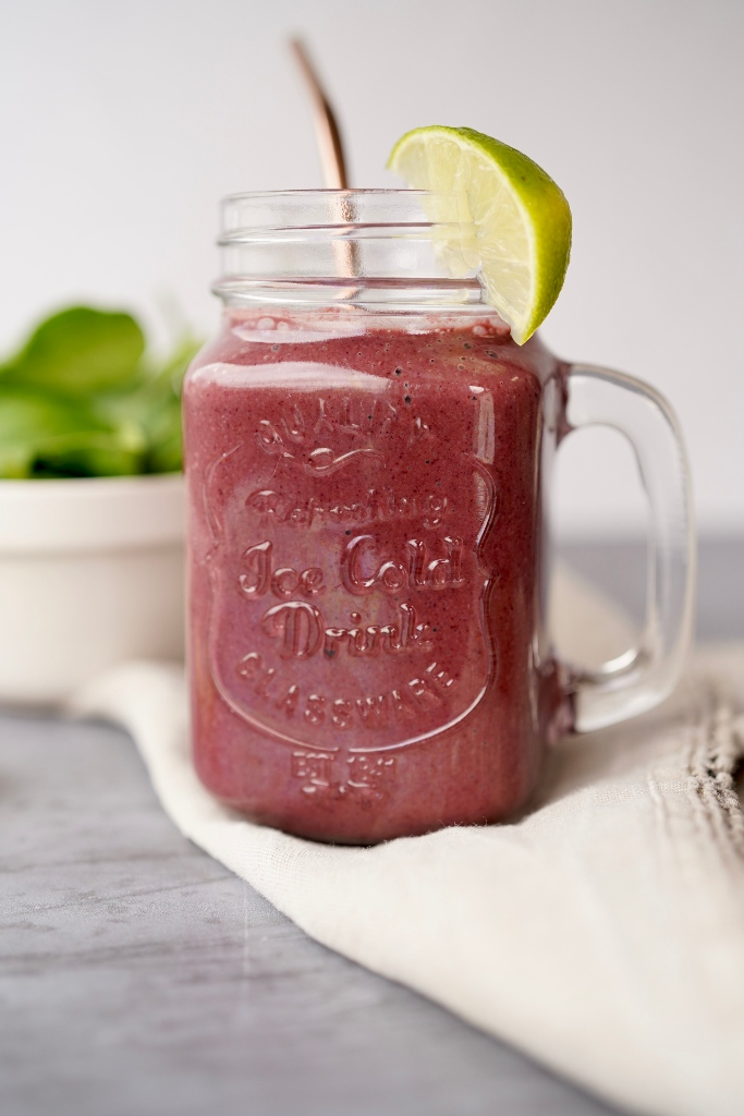 the healthy blueberry spinach smoothie in a glass with a straw and a piece of lime to serve