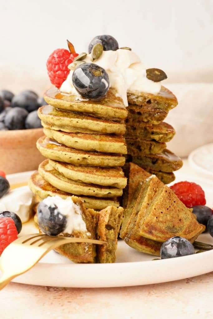a stack of matcha pancakes topped with vegan yogurt, blueberries, raspberries and maple syrup, with a section cut through all of the pancakes as if being eaten.