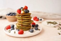 a stack of matcha pancakes topped with vegan yogurt, blueberries, raspberries and maple syrup